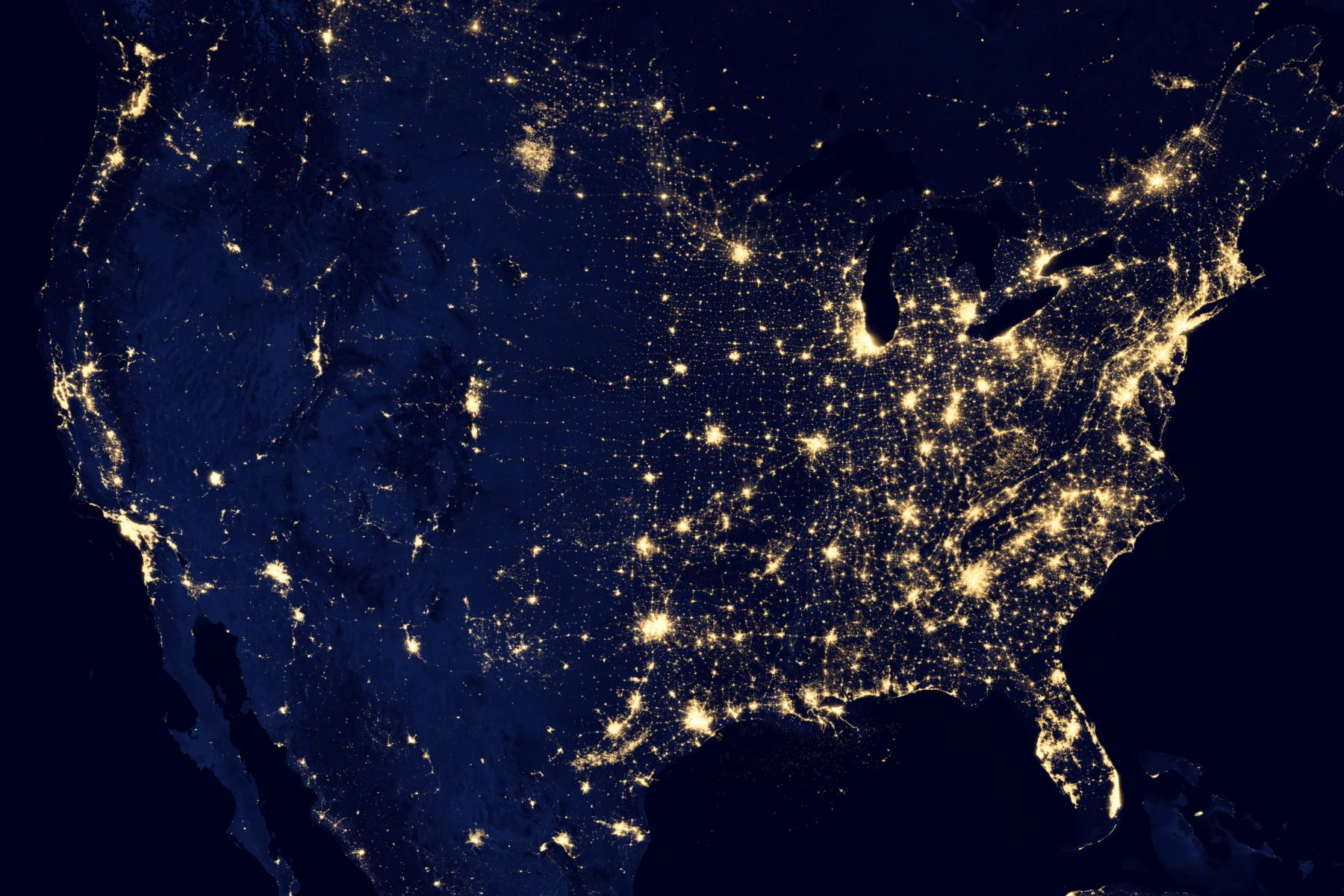 Satellite image of the united states at night shows yellow light of cities.