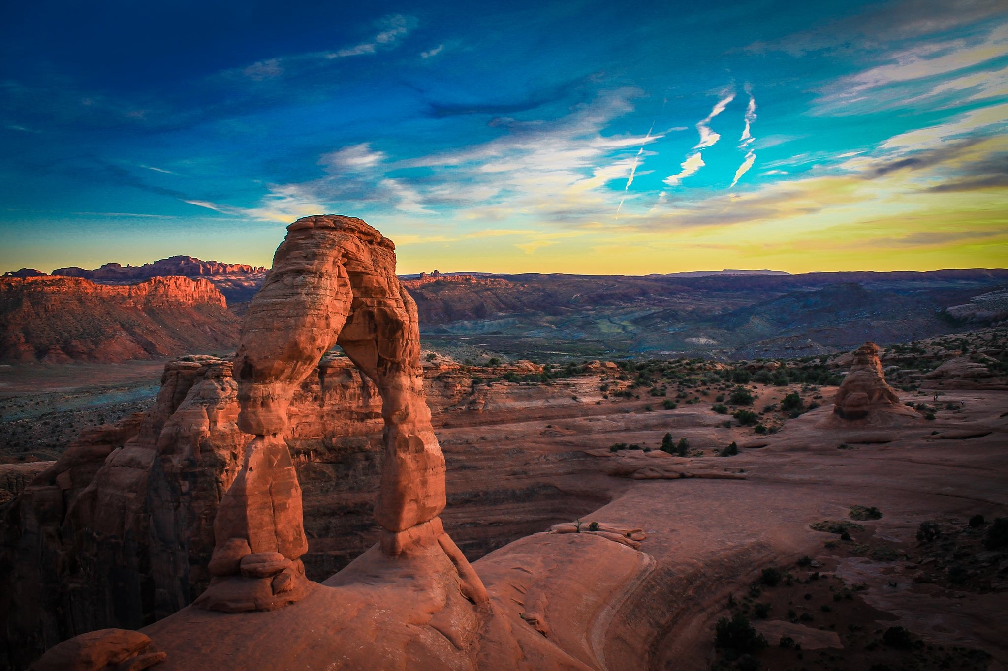 Delicate arch at sunset. The sky fades from indigo to turquoise to lemonade. The glowing sandstone is a peachy orange with shadows of raw sienna.