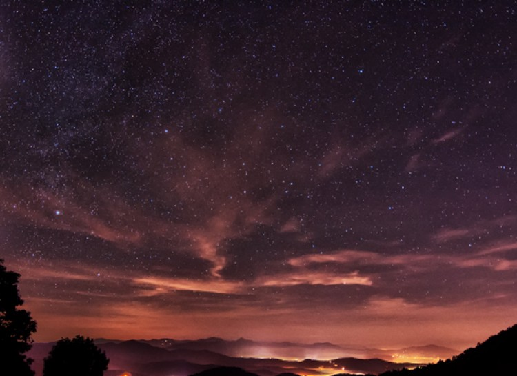 view of a peach and indigo sky scattered with clouds and stars. Lights of the valleys glow below.