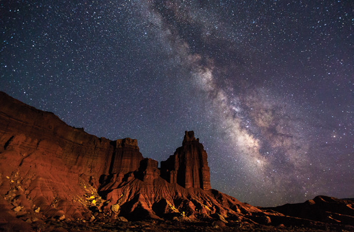 Milky way cascading over the tower and castle-like sandstone formations of Capitol Reef.