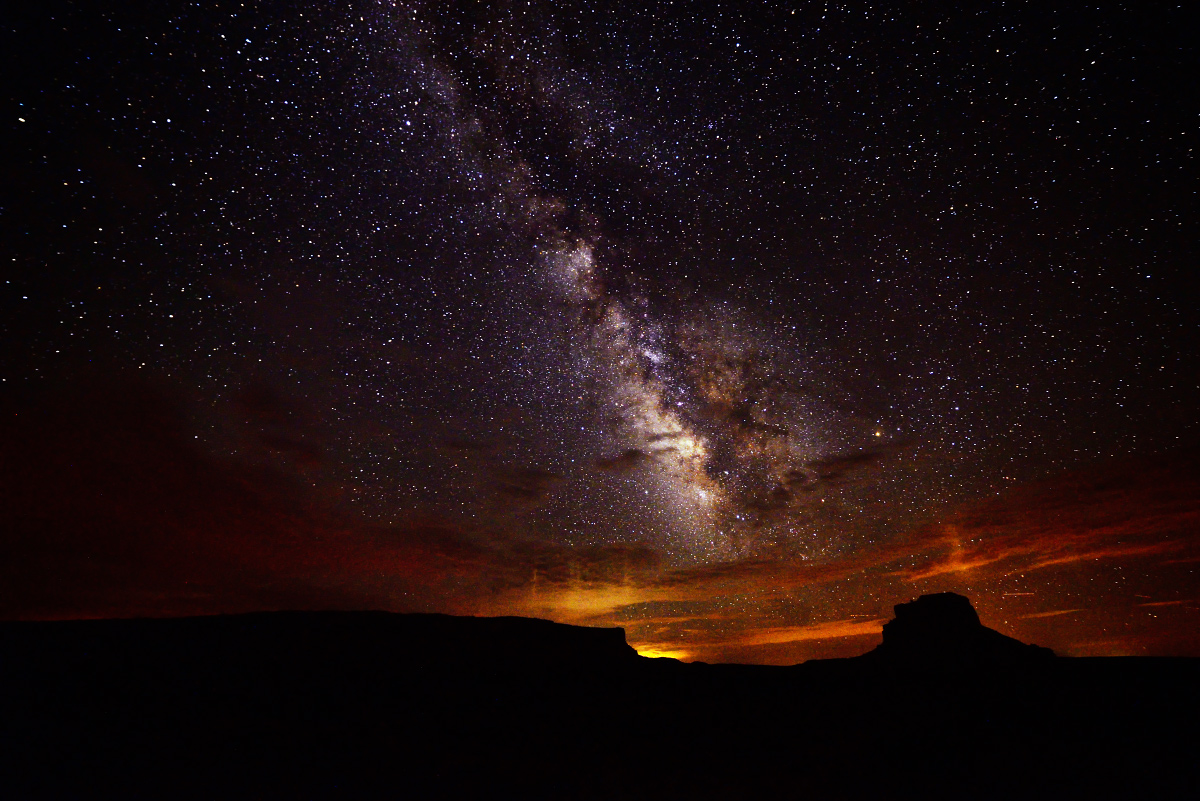 Silhouette of buttes and bluffs while the horizon glows orange and red, and the milky way glows pearly white above.